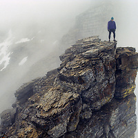 A mountaineer stands on a foggy outcrop of Mount Gould in Montana's Glacier National Park.