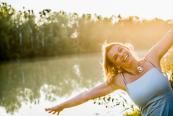 Portrait of a beautiful woman laughing hysterically by river, Germany, Bavaria