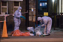 © Licensed to London News Pictures. 25/07/2017. LONDON, UK.  Police forensic officers at the crime scene cordon on Burnham Street just off Roman Road this evening near Singh supermarket.  Two males in their late teens have been taken to hospital for treatment after an unknown liquid was thrown at them. Photo credit: Vickie Flores/LNP