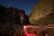 Red lights trace the path of biologists as they work late into the night during a noctrunal bat survey during this time exposure. The Nature Conservancy's Dutch Henry Falls preserve in central Washington.