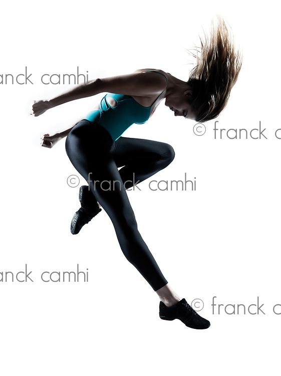 Side view of a young beautiful girl doing gymnastic jump in studio on white background