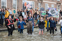 © Licensed to London News Pictures. 15/03/2019. Bristol, UK. Youth Strike 4 Climate outside Bristol City Hall on College Green. Young people wade through the moat in front of Bristol City Hall to show their views about climate change. The Bristol event is part of a UK wide and international day of protest as students and school pupils across the world miss classes, striking to protest a lack of governments' action to combat the climate crisis. The international movement was started by Swedish student Greta Thunberg. Photo credit: Simon Chapman/LNP