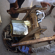 A hawker uses a portable machine to make sugar cane juice near Chandni Chowk in Old Delhi as people wait their turn for a drink. The green muddy sweet juice is a common delicacy in India.