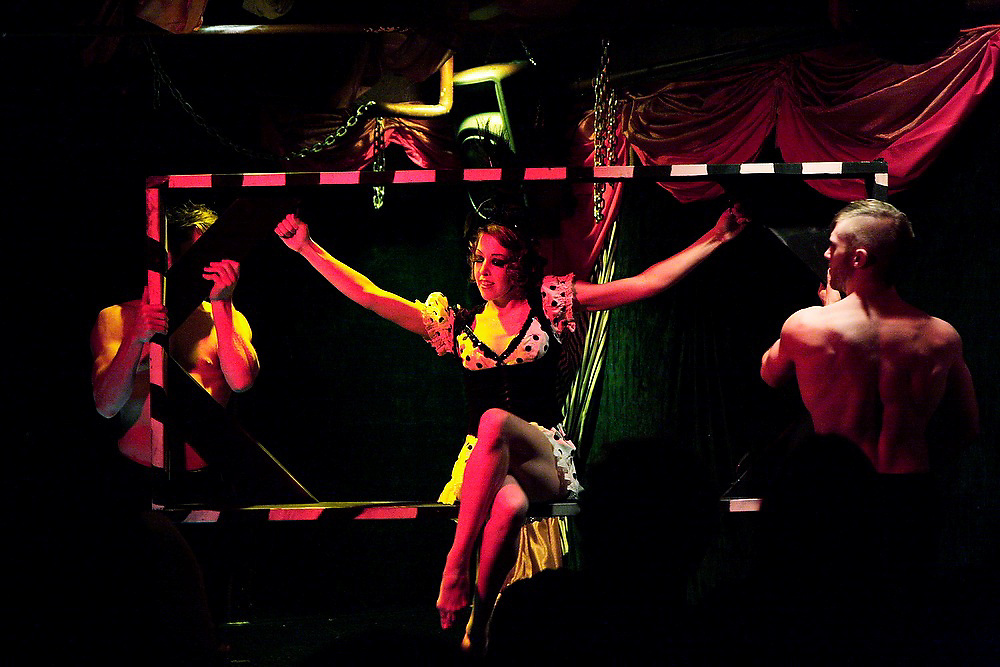 A woman sits in a door frame carried by two men at a burlesque cabaret performance at the Can Can in Seattle, Washington.