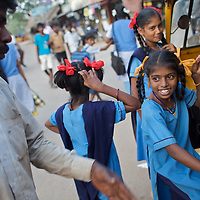 """Vijita (facing away) and Vijyashree (in yellow ribbons) Viswanathan head home to their fishing village in a rickshaw after a day at the Government Girls High School, Venugopalapuram, Cuddalore...Vijita (age 14) and Vijyashree (age 11) Viswanathan lost their mother and brother to the tsunami in 2004. They continue to live in the fishing village of Thazanguda with their father Viswanathan, his second wife Kayalvizhi and their two children Sanjay (age 3) and Monica (age 1). ..Until the beginning of the 2009 academic year in June, Vijita and Vijyashree attended the local Thazanguda school. This village school teaches pupils only until the 8th Standard and with Vijita now entering the 9th, it was decided that the two daughters remain together and both travel 3km to the local town school: the Government Girls High School, Venugopalapuram in Cuddalore. ..At the same time Viswanathan decided he would cease day-to-day care of his daughters and place them in the Government Home for Tsunami Children, also in Cuddalore. This was not a move welcomed by either Vijita or Vijyashree and one afternoon after just two weeks at the orphanage, the two girls ran away. At roll call in the orphanage that evening the alarm was sounded and the two sisters were eventually located in Thazanguda waiting for their father and Kayalvizhi who were both away at the time. Realising his daughters' unhappiness, Viswanathan then took them out of the Government home. ..According to her class teacher, Vijita often compares her step-mother to her mother and concludes that she wants her mother back. Vijita confides in her teachers that her stepmother is forever demanding that she and her sister Vijyashree undertake housework. This frustration at home is tempered by the genuine love both sisters have for their father and two younger siblings Sanjay and Monica. Vijita expresses a lonelyness without her mother. Vijita's class teacher Pushpavalli concludes that """"Vijita wants something else beyond the love of he"""