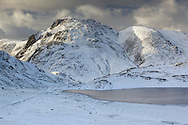 Winter snow-covered south-east face of Great Gable from Sprinkling Tarn.