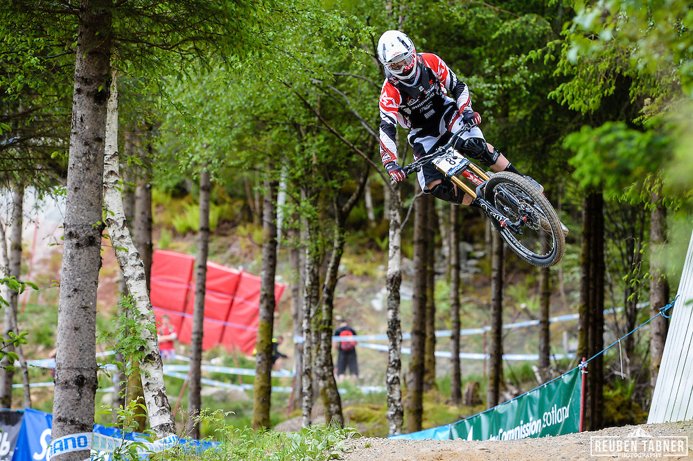 09.06.2013 Fort William, Scotland. George Brannigan of Trek World Racing adds some style to his race run during the Men's Elite Downhill  Final for the UCI Mountain Bike World Cup in Fort William.