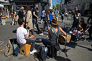 Buskers playing guitar on Portobello Road Market in Notting Hill, West London, England, United Kingdom. People enjoying a sunny day out hanging out at the famous Sunday market, when the antique stalls line the street.  Portobello Market is the world's largest antiques market with over 1,000 dealers selling every kind of antique and collectible. Visitors flock from all over the world to walk along one of London's best loved streets.