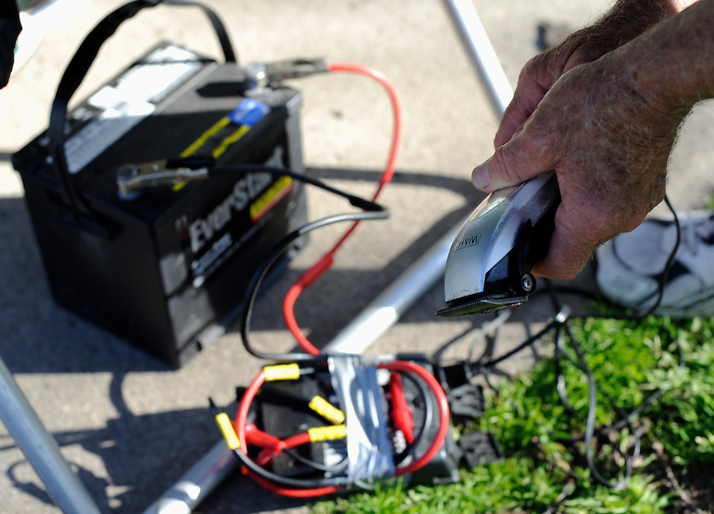 Anthony Cymerys checks his clippers that are connected to a car battery through a power inverter in Hartford, Conn.