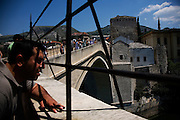 """Tourists looking out at the Neretva river...Divers and tourists at Mostar's famous Old Bridge (Stari Most) in Bosnia and Herzegovina. This bridge is the city and region's biggest tourist attraction and there are busses full of tourists coming in from Sarajevo and Dubrovnik, Croatia. For 25euros tourists can train to jump from the bridge themselves, under supervision from the """"professional"""" Mostar divers known as the Mostari. .."""