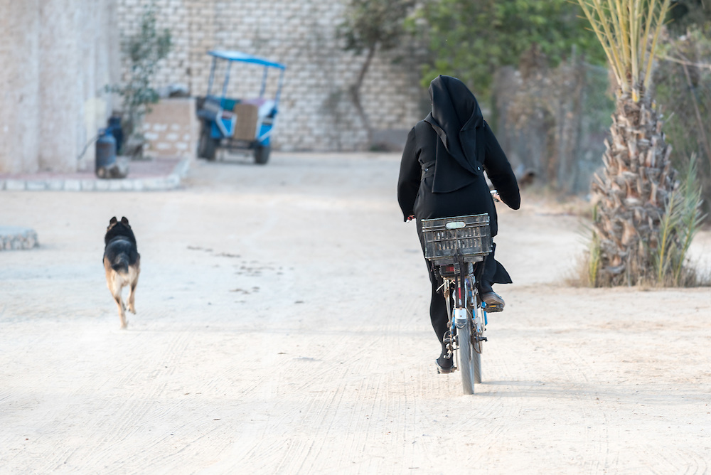 16 December 2016, Cairo, Egypt: Coptic Orthodox nun Sister Haria riding her bike accompanied by a German Shepherd, at the Anaphora Institute, a Coptic Orthodox retreat and educational centre located north-west of Cairo.
