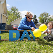 Danielle Strong, left, and her son, Trent Futey, 5, of Rossford, set up surprise birthday signs outside 7-year-old Deklin Collins' Woodville Road home in Oregon, Ohio, on Thursday, May 7, 2020. They are family friends of Deklin's family, and they decided to surprise Deklin for his 7th birthday with signs encouraging motorists to honk as they pass by. They set up the decorations while Deklin and his family were out camping. THE BLADE/KURT STEISS
