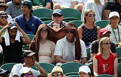 Spectators shelter from the sun on day four of the Wimbledon Championships at The All England Lawn Tennis and Croquet Club, Wimbledon.