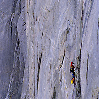 BAFFIN ISLAND, Nunavut, Canada. Alex Lowe (MR) uses drill to place bolt for belay station on  Great Sail Peak, an Arctic big wall rock climb.