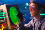 Virtual reality in air traffic control (ATC) systems. Bill Wiseman from the University of Washington Human Interface Technology Laboratory, Seattle, demonstrating how ATC might operate in the future. Optical fiber sensors in his black data glove & the pink-rimmed micro-laser scanner glasses connect the operator with a virtual, computer-generated, 3-D image of the airspace he is controlling. Through raising his gloved hand to touch an icon (projected image) of an approaching jet, he is placed in instant voice communication with the pilot. This photograph was taken with the cooperation of SEA/TAC international airport, Seattle. MODEL RELEASED. (1990)