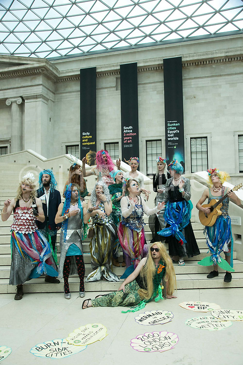 """Bp-or-not-Bp stage a splash mob dressed as merfolk at the British Museum in protest against the continued sponsorship by the oil company Bp, in particular against  the sponsorhsip of the exhibition 'Sunken Cities"""". The merfolk sang and performed around the museum with placards rejoycing BP and the rising sea levels because as merfolk they will benefit from climate change. The public were invited to add their thoughts on future sunken cities around the world and to participate in the ongoing debate on oil and climate change. (photo by Kristian Buus/In Pictures via Getty Images)"""