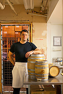 Barrel-aged cocktails made by Clyde Common's restaurant bartender, Jeffery Morgenthaler, in Portland, Oregon.  Pictured here is the Jeffery with several of his aging barrels in the room where the mixtures are produced.
