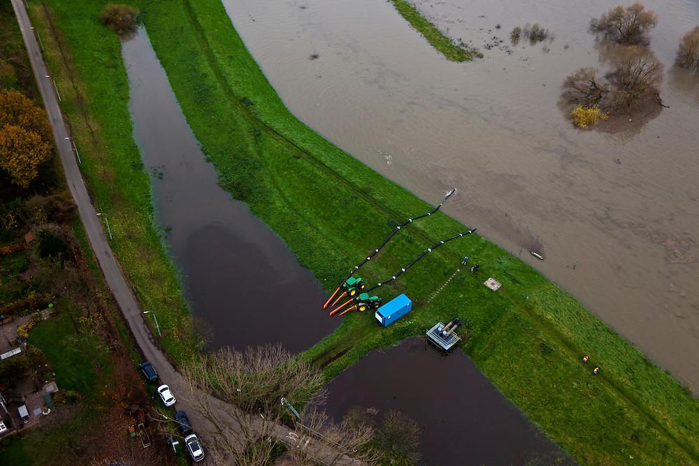 Nederland, Limburg, Gemeente Venlo, 15-11-2010. Maasdijk bij Blerick. De beken in het achterland van Blerick kunnen  het water niet afvoeren door de hoge waterstaat van de Maas. Om de wateroverlast te bestrijden heeft het waterschap extra pompen opgesteld, inclusief twee door tractoren aangedreven extra noodpompen. Op de dijk filmen tv ploegen de opstelling..Maasdijk at Blerick. The streams in the hinterland of Blerick water can not drain the into the river  Meuse because of the high water level. .Regional Water Authority has placed pumps, including two extra emergency pumps that are driven by tractors. On the dike TV crews filming..luchtfoto (toeslag), aerial photo (additional fee required).foto/photo Siebe Swart