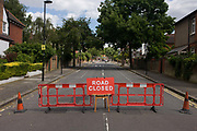 Closed Road during a street party in the south London borough of Lambeth in SE24. Lambeth council have allowed the blocking off of this small residential street and house owners are erecting the bunting that stretches across the road in advance of a street party in which neighbours bring out tables and food for all to enjoy. The barrier stops local traffic from turning into this street.