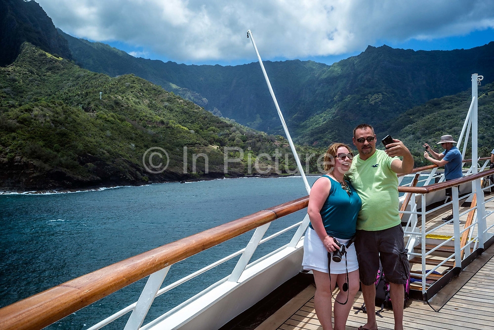 Tourists on board a cruise ship photograph themselves in front of Hiva Oa, Marquesas Islands, French Polynesia<br /> Hiva Oa is the second largest island in the Marquesas Islands, an overseas territory of France in the Pacific Ocean.