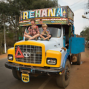 Two boys sits cross leg, in a yoga position, on top of a truck in India.