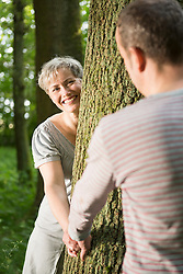 Mature couple playing in forest, smiling
