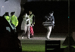 © Licensed to London News Pictures. 02/02/2020. Brize Norton, UK. Two passengers, one carrying a baby in a carry cot, evacuated from Wuhan in China disembark at RAF Brize Norton in Oxfordshire. On Friday 83 Britons were flown from the centre of the coronavirus outbreak to RAF Brize Norton and then transported to quarantine for 14 days at Arrowe Park Hospital on the Wirral. Photo credit: Peter Macdiarmid/LNP