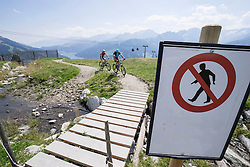 Two mountain bikers riding on bicycle trail with warning sign, Zillertal, Tyrol, Austria