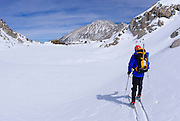 Backcountry skier crossing Treasure Lakes in Little Lakes Valley, Inyo National Forest, Sierra Nevada Mountains, California