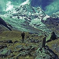 A trekker stands below Annapurna South in the Annapurna Sanctuary, Nepal.