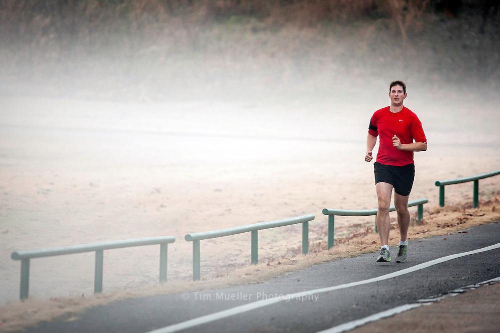 A jogger runs up Dalrymble Dr. at City Park in Baton Rouge, La.