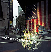 "Attending to a floral memorial of Lillies in a 5th Avenue store front in mid-town Manhattan. In the days following the September 11th attacks, a store window dresser is seen through the glass with Fifth Avenue reflected behind. The words ""In Memory and Gratitude"" are written in block capitals on the window and a passer-by walks briskly past the large floral display and the large US flag that hangs vertically in mourning for those killed and those heroes helping to uncover their remains in the debris. America sought to express their anger and patriotic unity by installing these shrines in the frontages of businesses and in homes as New Yorkers try to pick up the pieces of their lives."