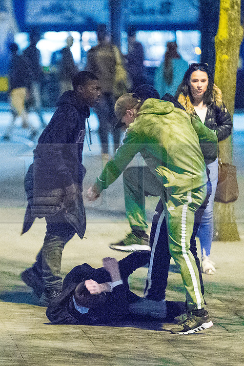 © Licensed to London News Pictures . 07/04/2017 . Manchester , UK . 7th in a sequence . Five youths on one as a fight breaks out in which a man's head is kicked and stamped upon , in Piccadilly Gardens . Greater Manchester Police have authorised dispersal powers and say they will ban people from the city centre for 48 hours , this evening (7th April 2017) , in order to tackle alcohol and spice abuse . Photo credit : Joel Goodman/LNP