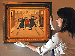 © Licensed to London News Pictures. 11/11/2011. London, UK. A woman holds Laurence Stephen Lowry's Home form the Pun, oil on canvas, 1944 estimated to fetch 400,000 - 600,000 GBP. Sotheby's preview of Modern and Post-War British Art which will offered for sale at auction on 15th November 2011. Photo credit : Stephen Simpson/LNP