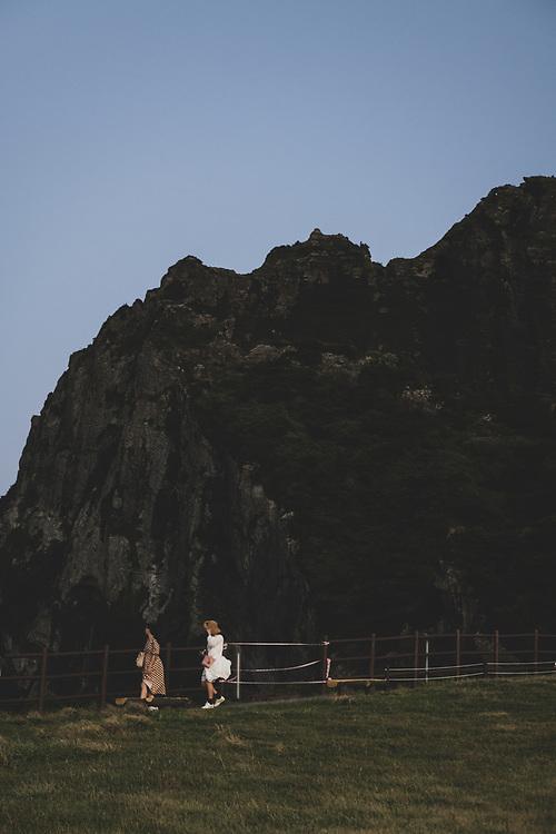 Jeju Island, South Korea - September 13, 2019: Two women walk on a path above the sea at Seongsan Ilchulbong, an archetypal tuff cone and national landmark, located on Jeju Island, South Korea (September 13, 2019)
