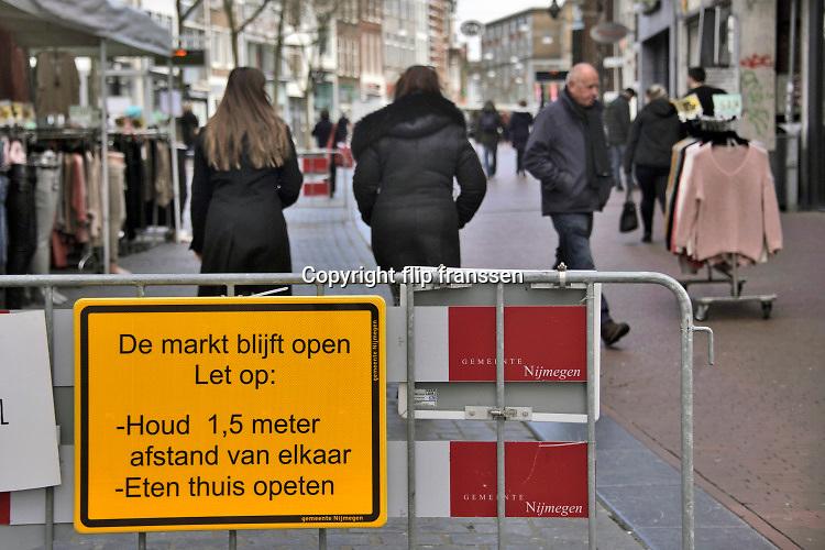 Nederland, Nijmegen, 30-3-2020 In de binnenstad van Nijmegen is het markt. Die is open, maar er zijn maar weinig klanten en ook veel marktkooplui zijn niet gekomen. Sommigen hebben vakken gemaakt van afzetlint of bakken om de bezoekers te dwingen afstand van 1,5 ,anderhalve, meter te houden . Foto Flip Franssen