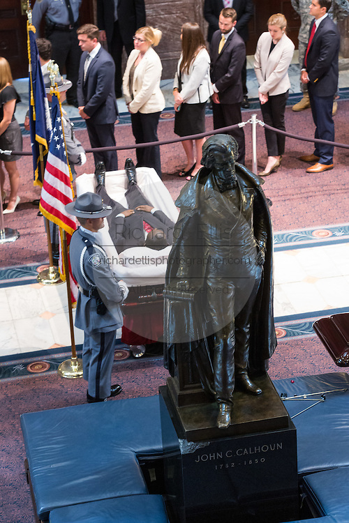 Mourners pause to view the body of slain State Senator Clementa Pinckney lying in State in the Capitol under the statue of John C. Calhoun during public visitation June 24, 2015 in Columbia, South Carolina. Pinckney is one of the nine people killed in last weeks Charleston church massacre.