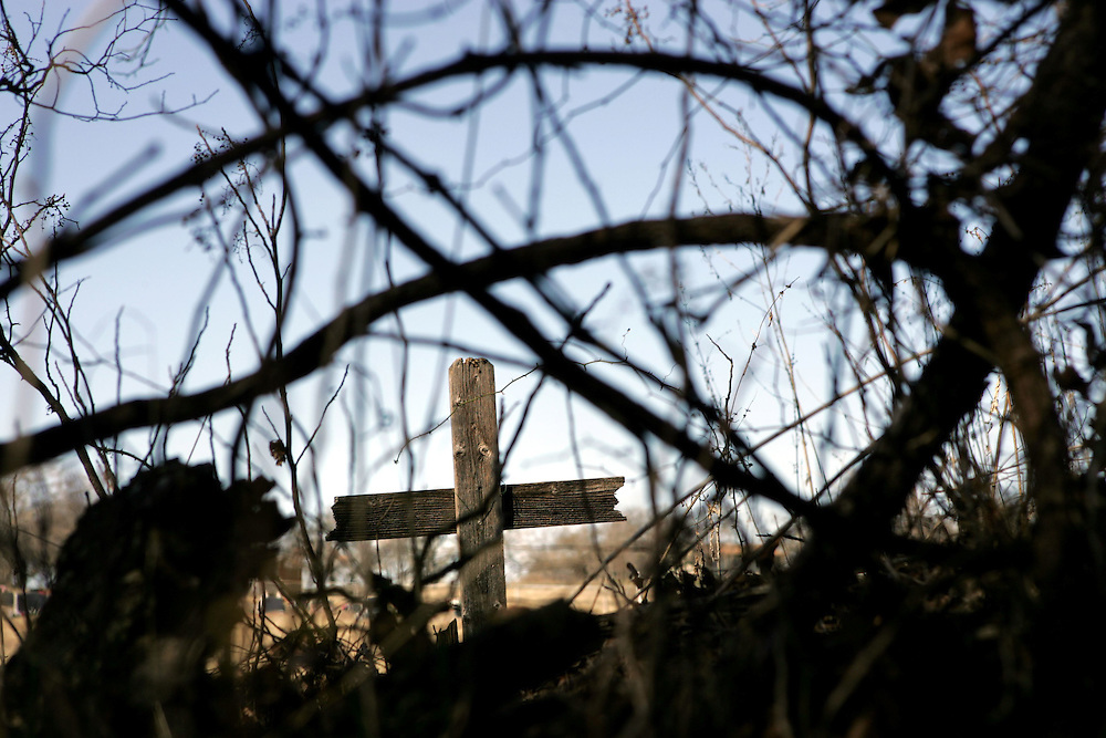 A wooden cross sits hidden in the back of the Aurora Cemetery in Aurora, Texas.
