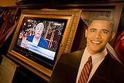 BBC News coverage shows John Simpson speaking behind a life-size cardboard cut-out of Barack Obama during 2008 elections