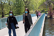 UNITED KINGDOM, London: 20 April 2020<br /> Members of public walk through St James's Park in central London in the sun shine this afternoon whilst wearing a mask due to the COVID-19 pandemic. The sunny weather is set to continue throughout the week with temperatures set to reach 20 degrees Celsius.