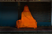 Large Buddhist figures, wrapped in traditional orange cloth, on street. Situated in the heart of Bangkok, near the famous swing, is a series of streets and alleyways dedicated to the manufacture of Buddhist and Hindu icons together with other religious paraphernalia.
