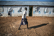 Nyajouk Chuol Bil, 18, walks toward the classroom at a school run by UNHCR inside Bidibidi refugee settlement in Uganda. When a small fighting broke out in the summer of 2015, she hid in the UN compound in Juba. When she went outside the compound to buy sandals, she was met with four Dinka soldiers with AK-47. She got pregnant from the rape and gave birth to a daughter. She was separated from her parents and hasn't heard the whereabout of them.  Now a senior 1 grade in the secondary school, she goes to school inside the refugee camp, but worries that there's very few people who could babysit the baby when she is away. She said she wanted to be an accountant or work in a bank in the future.