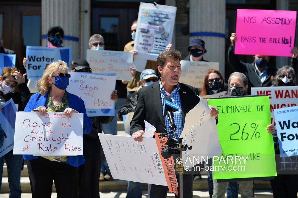Mineola, New York, USA. April 26, 2021. Front row, L-R,  CLAUDIA BORECKY DAVE DENENBERG, Co-Directors of CAWS (Clean Air Water Soil), are speakers at rally. Faced with a 26% rate increase from New York American Water going into effect May 1, 2021, activists and residents who are NYAW customers rally to urge NYS Assemby to push through legislation, before that date, corresponding with NYS Senate Bill S989A to establish a Nassau County Water Authority and except water works corporations in counties of populations over one million from a special franchise tax.