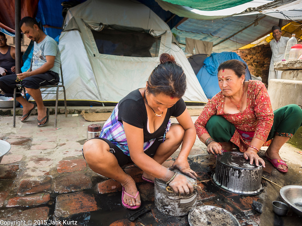 04 AUGUST 2015 - BUNGAMATI, NEPAL: Women do their dishes in front of their tents in Bungamati, a village about an hour from Kathmandu. Three months after the earthquake many families still live in tents scattered around the village. The Nepal Earthquake on April 25, 2015, (also known as the Gorkha earthquake) killed more than 9,000 people and injured more than 23,000. It had a magnitude of 7.8. The epicenter was east of the district of Lamjung, and its hypocenter was at a depth of approximately 15km (9.3mi). It was the worst natural disaster to strike Nepal since the 1934 Nepal–Bihar earthquake. The earthquake triggered an avalanche on Mount Everest, killing at least 19. The earthquake also set off an avalanche in the Langtang valley, where 250 people were reported missing. Hundreds of thousands of people were made homeless with entire villages flattened across many districts of the country. Centuries-old buildings were destroyed at UNESCO World Heritage sites in the Kathmandu Valley, including some at the Kathmandu Durbar Square, the Patan Durbar Squar, the Bhaktapur Durbar Square, the Changu Narayan Temple and the Swayambhunath Stupa. Geophysicists and other experts had warned for decades that Nepal was vulnerable to a deadly earthquake, particularly because of its geology, urbanization, and architecture.    PHOTO BY JACK KURTZ