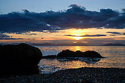 Chugach Mountains and setting sun from the shore of Herring Bay, Prince William Sound, Alaska