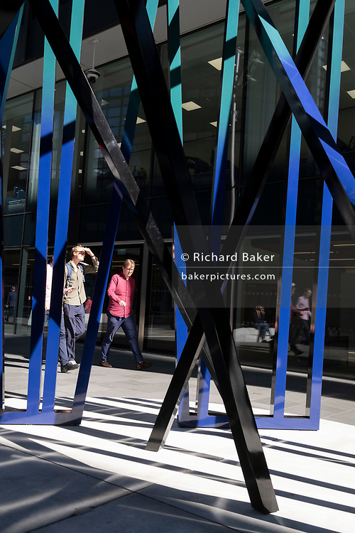 City workers walk past the sculpture entitled 'Cosmos', an artwork by Eva Rothschild in the City of London, the capital's financial district, on 24th September 2021, in London, England. Cosmos (2019) is composed of three 3.5m high slatted structures which lean and support each other and is part of the summer's Art In The City' project.