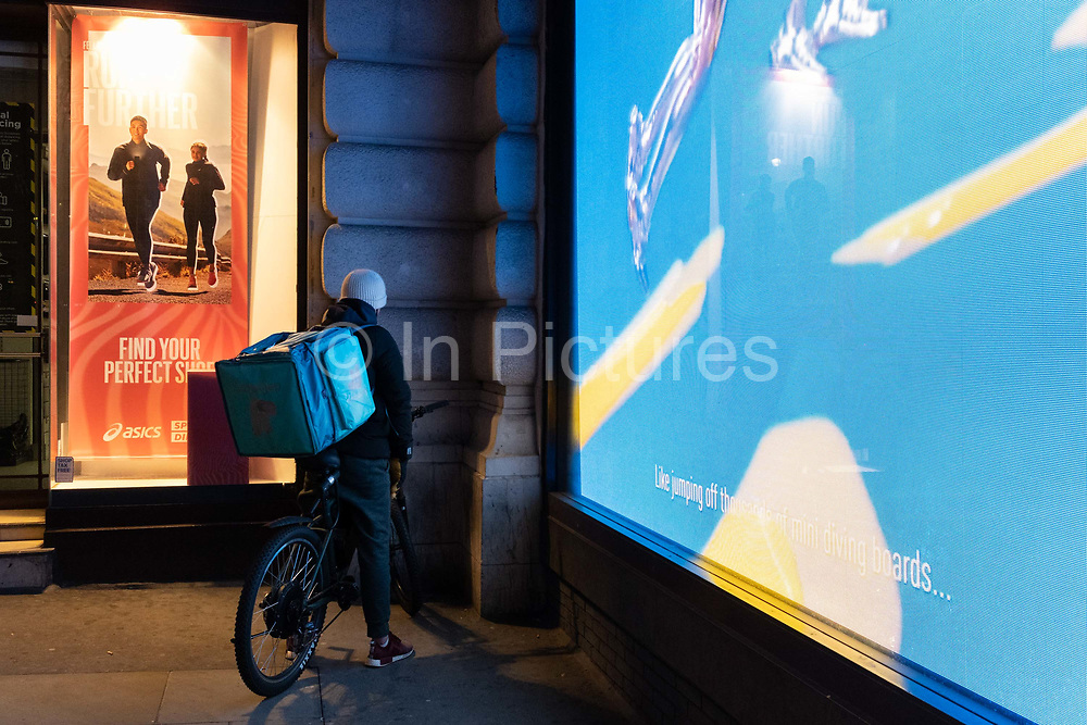 A Deliveroo delivery rider finds a dark corner of a bright Piccadilly Circus to check his phone during the third lockdown of the Coronavirus pandemic, 5th February 2021, in London, England.