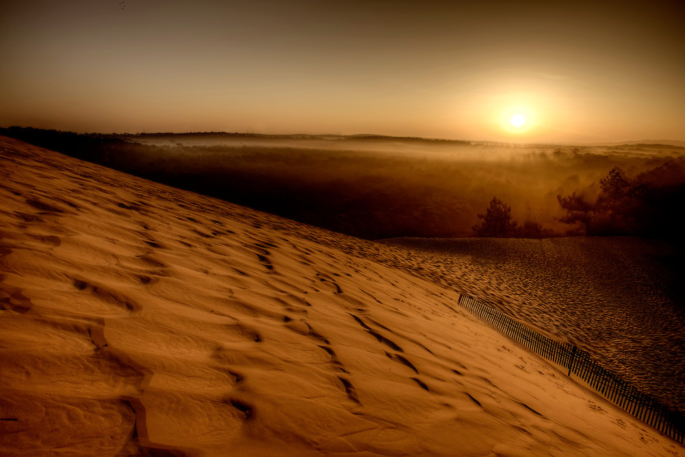 """At 60Km from Bordeaux, in the South of the Arcachon Bay, it is the highest dune in Europe, the Great Dune of Pila (or Pilat). This dune reaches a height of 107m. At this summit, the view is spectacular with the ocean coast, the inlet of the Bay, the large pine forest and, when the sky is very clear, the Pyrenees Range. The Great Dune of Pyla is located on the """"La Teste de Buch"""" district (Gironde) and it is a national listed landscape."""