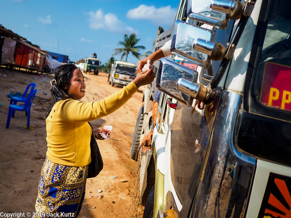 """14 FEBRUARY 2019 - SIHANOUKVILLE, CAMBODIA: A Cambodian woman who moved to Sihanoukville with her family sells an energy drink to a Cambodian truck driver at a construction site in Sihanoukville. She said they moved to Sihanoukville about a month ago hoping to find jobs in the Chinese financed boom in Sihanoukville. Her husband works as a construction laborer and she runs a small drink and snack stand. There are about 80 Chinese casinos and resort hotels open in Sihanoukville and dozens more under construction. The casinos are changing the city, once a sleepy port on Southeast Asia's """"backpacker trail"""" into a booming city. The change is coming with a cost though. Many Cambodian residents of Sihanoukville  have lost their homes to make way for the casinos and the jobs are going to Chinese workers, brought in to build casinos and work in the casinos.      PHOTO BY JACK KURTZ"""