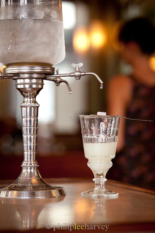 A traditional way of drinking absinthe. Water is chilled in a bowl of ice, and a tap is slowly opened. The water drips down through a cube of sugar to sweeten the absinthe. Seen here in a brasserie in Paris, France